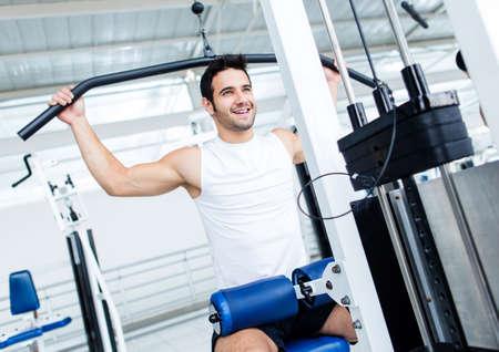 hombres haciendo ejercicio: Hombre apto que ejercita en el gimnasio en una m�quina Foto de archivo