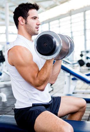 levantando pesas: Hombre fuerte en el gimnasio levantando pesas Foto de archivo
