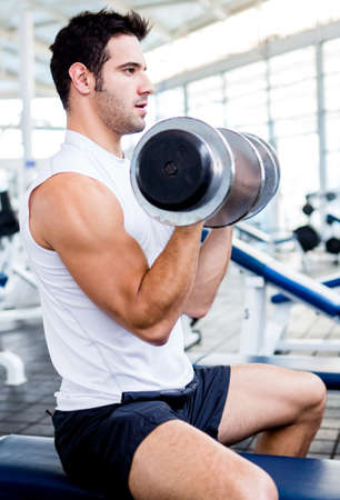 Strong man at the gym lifting heavy weights  photo