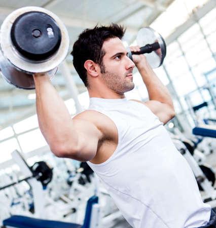 pesas: Hombre guapo gimnasio levantando pesas pesadas