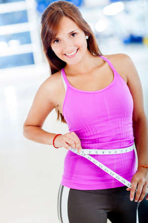 Fit woman measuring her waist and smiling photo