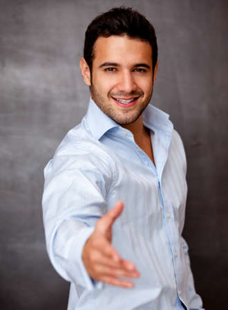 Handsome business man with hand extended handshaking  photo