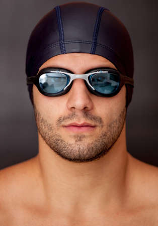 Professional male swimmer wearing goggles and a hat  photo