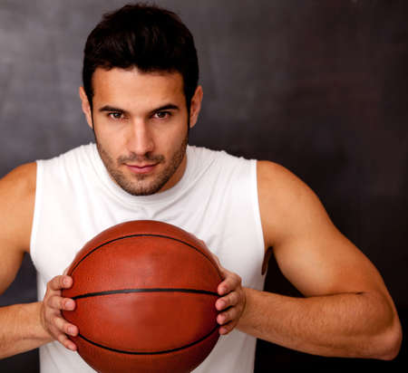 Competitive male basketball player holding the ball  photo
