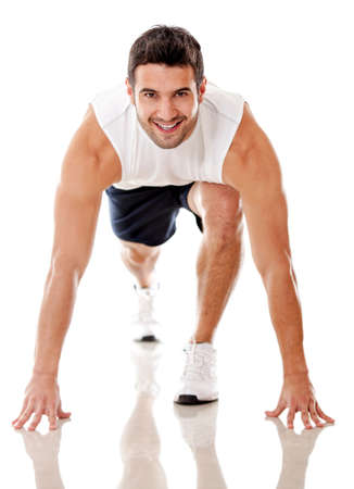 tracksuit: Competitive male athlete ready to run - isolated over a white background  Stock Photo