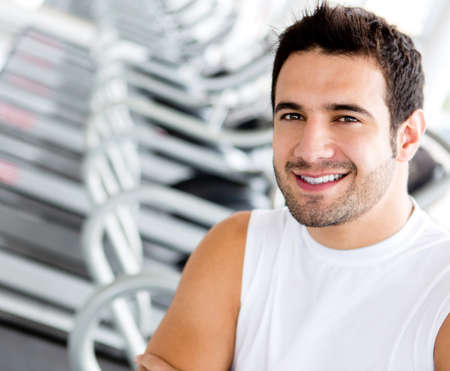 Handsome man at the gym looking happy  photo