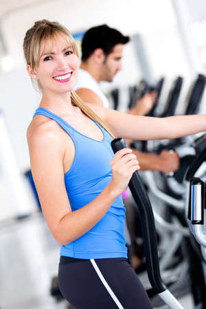 Happy woman training at the gym on cross trainer  photo