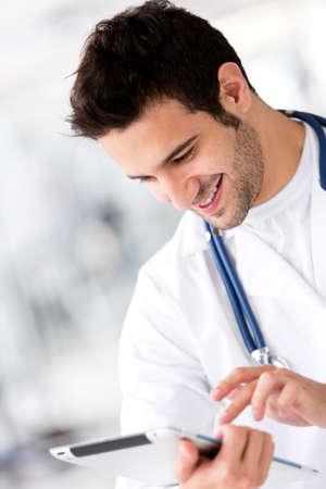 male doctor: Amichevole medico di sesso maschile in possesso di un computer tablet e sorridente Archivio Fotografico