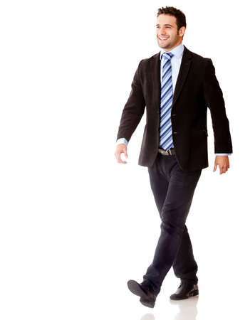 Business man walking and looking happy - isolated over white background  photo