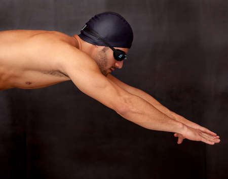 dive: Professional male swimmer diving wearing a hat and goggles  Stock Photo