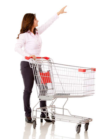Woman with a shopping cart reaching for something - isolated over white  photo