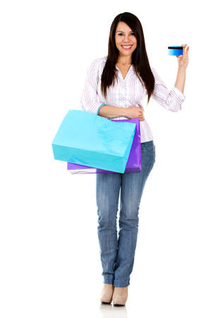 Woman on a shopping spree holding credit card - isolated over white  photo