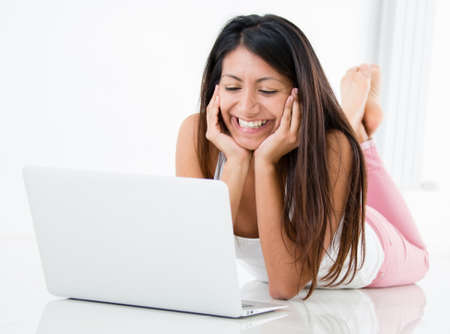 videos: Happy woman chatting online on her laptop computer  Stock Photo