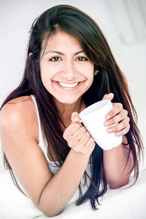 Happy woman drinking coffee - isolated over a white background  photo