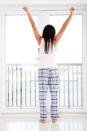 Woman at home just waking up and looking through the window  photo