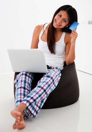 Happy woman shopping online from her laptop  photo