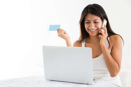 Woman shopping online from home and talking on the phone  photo