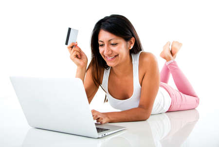 Woman online shopping on a laptop computer - isolated over white  photo