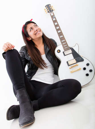 Woman with an electric guitar thinking of being a rock star  photo