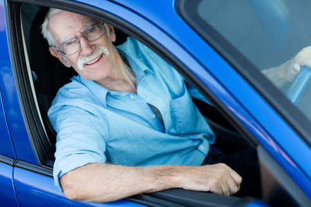 Happy elder man driving a blue car  photo