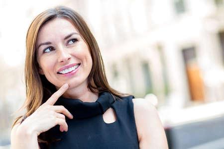 mujer pensativa: Retrato de una mujer pensativa mirando hacia arriba al aire libre Foto de archivo