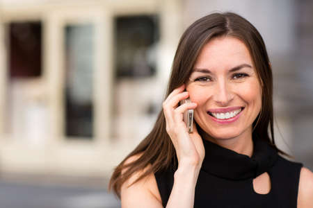 gente comunicandose: Mujer de negocios feliz hablando por el tel�fono al aire libre