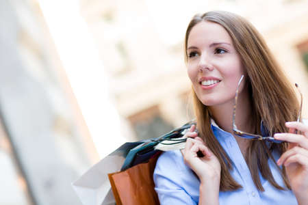Beautiful female shopper holding shopping bags looking happy  Stock Photo - 15503052