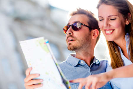 Couple of tourists holding a map and having fun on their holidays  Stock Photo - 15503051