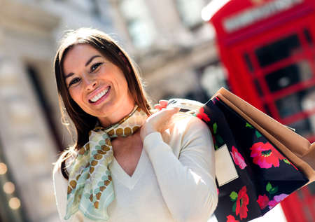 Woman on a shopping spree in London looking very happy  photo