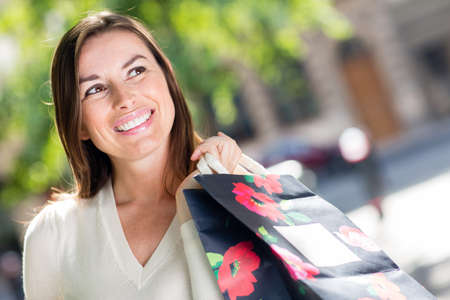 Thoughtful female shopper smiling and holding shopping bags  photo