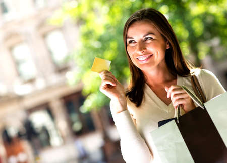 Shopping woman holding a credit card and smiling  photo
