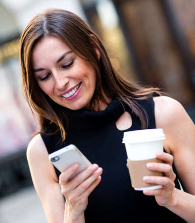 sms text: Busy business woman texting on her cell phone Stock Photo