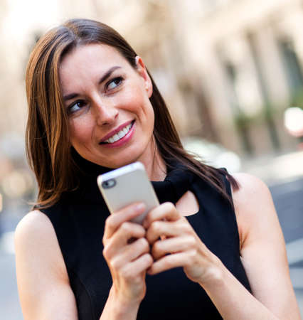 Woman replying a text message on her mobile phone  photo