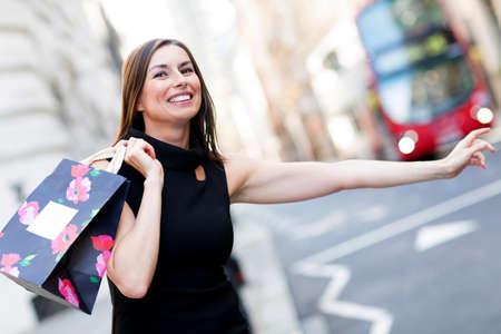 taxi: Mujer de compras con su brazo extendido cogiendo un taxi Foto de archivo