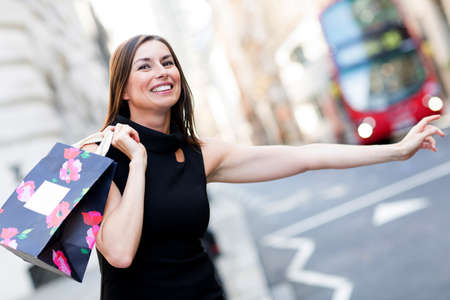 purchases: Shopping woman with her arm extended grabbing a taxi