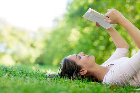 mujer leyendo libro: Mujer tranquila que goza leyendo un libro al aire libre