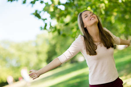 Relaxed woman at the park enjoying her freedom  Stock Photo - 15288679