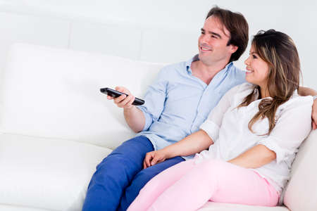 Loving couple at home watching tv and smiling  photo