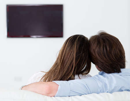 pareja viendo television: Pareja romántica viendo la televisión en su casa