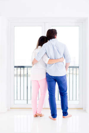 Romantic couple in their apartment looking through the balcony  photo