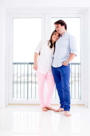 Romantic couple at home hugging and looking happy  photo
