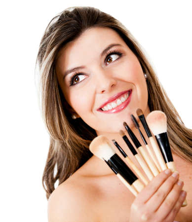 make up brushes: Beauty portrait of a woman holding make up brushes - isolated over a white background