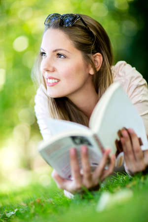 woman reading book: Thoughtful woman reading a book outdoors and smiling