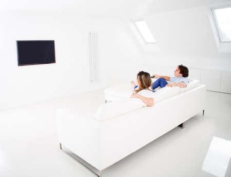 pareja viendo tv: Pareja viendo tv en casa mirando muy feliz