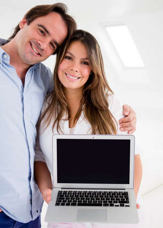 Couple hugging and holding a laptop at home  Stock Photo - 15250021
