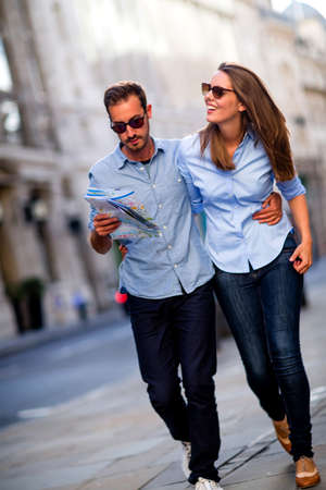 Happy couple walking outdoors sightseeing and holding a map  photo