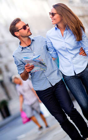 Couple of tourists walking outdoors and holding a map  Stock Photo - 15288701