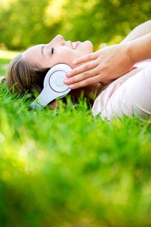 escuchando musica: Mujer que escucha la música con los auriculares en el parque