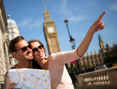 disoriented: Happy summer tourists in London holding a map  Stock Photo