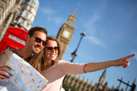 british man: Couple of tourists in London holding a map